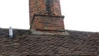 Mortar fillets are commonly used at the junction between peg tiles and a chimney (shown here), but lead flashings (shown below) are much more reliable.